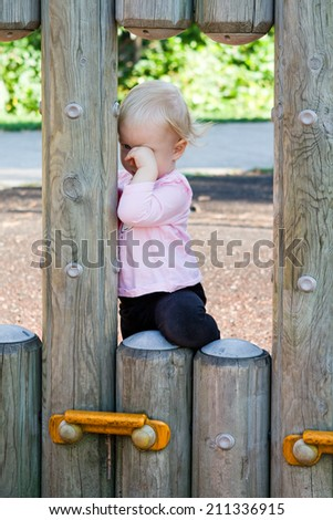 Little child girl crying on playground in loneliness. Childhood problems concept. - stock photo
