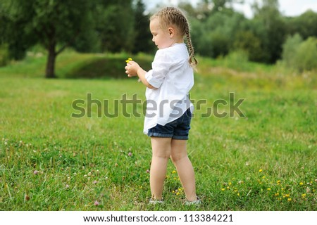 Little child girl gathering flowers on a meadow - stock photo