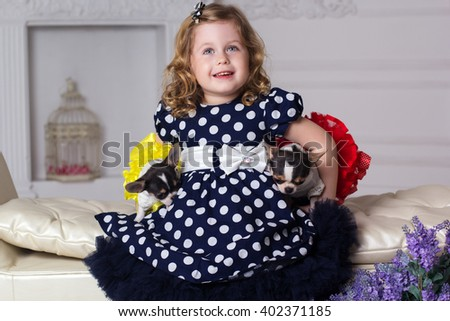 Little child girl is holding two dogs - stock photo