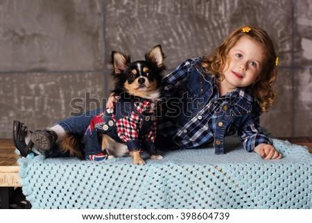 Little child girl is lying with black chuhuahua dog - stock photo