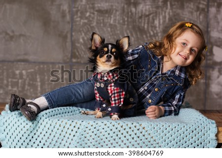 Little child girl is lying with chuhuahua dog - stock photo