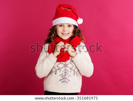 Little child girl is wearing santa hat isolated on red background - stock photo