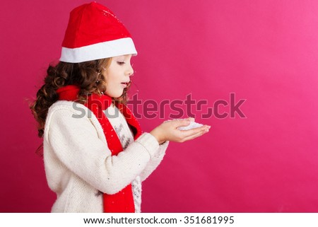 Little child girl is wearing warm clothes and santa hat isolated on red background - stock photo