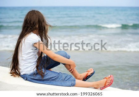 Little child girl looking at waves sitting on a ocean shore - stock photo