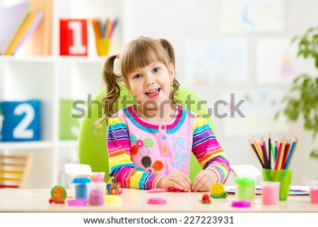 Little child girl playing with colorful clay