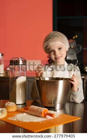 Little child girl sitting at table and playing with dough and flour, bakery, cooking - stock photo