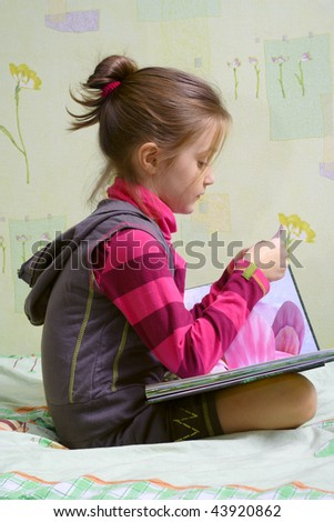 little child girl sitting on a bed and reading a book