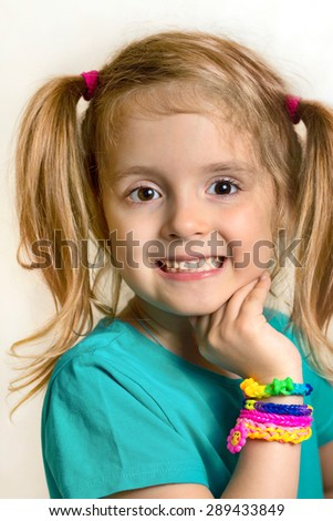 Little child girl smiling portrait with loom bracelets.Happy female caucasian kid closeup. - stock photo