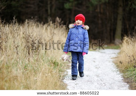 Little child girl walking along the road covered in first snow - stock photo