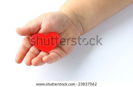 Little child hand holding red heart candy