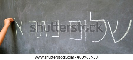 Little child hand writes Hello First Grade greetings in Hebrew (Shalom Kita Alef) on a chalkboard in Israeli primary school at the beginning of the school year. Education concept photo - stock photo