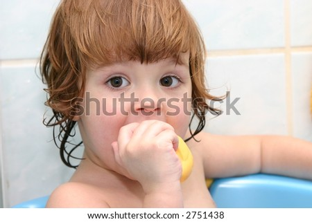 little child having a bath in small blue bathtub