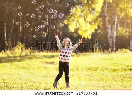 Little child having fun with bubbles soap in sunny autumn day - stock photo