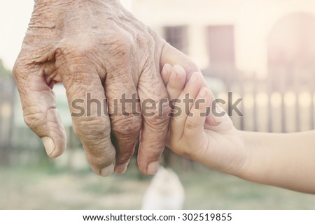 Little child holding her grandparent for hand,selective focus