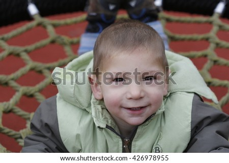 Little child in autumn jackets swinging in a swing outside in playground - stock photo