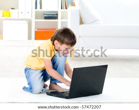 Little child in casuals playing on laptop at home - indoors