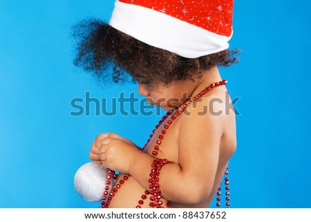 Little child in Christmas hat playing with toys - stock photo