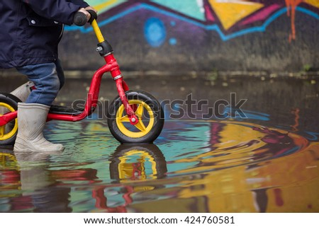 Little child in grey rubber boots cycling after rain.Toddler in a pair of grey rubber boots in a big puddle with graffiti wall reflection. Fun after rain. Boy on the bike on the street. - stock photo