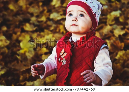 Little child in the autumn garden looks at the sky