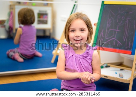 Little child is drawing with pieces of color chalk on the chalk board. Girl is expressing creativity and looking at the camera, smiling in a nursery, classroom or playroom. Concept of play, learning