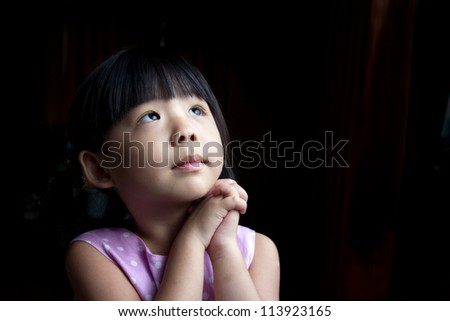 Little child is making a wish isolated in dark background - stock photo