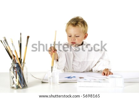 little child is painting with brush and paint - stock photo