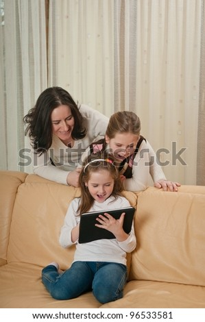 Little child is playing with tablet at home while her mother and sister are watching over shoulder