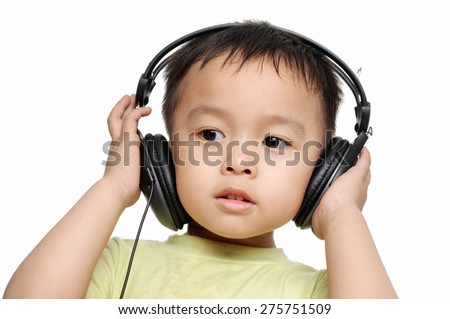 Little child listening music on white background