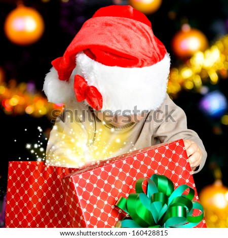 Little child looking into the box with gifts on the christmas holiday - indoors - stock photo