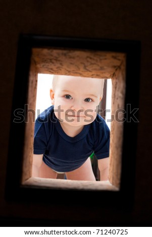Little child looks to hole in the wall - stock photo