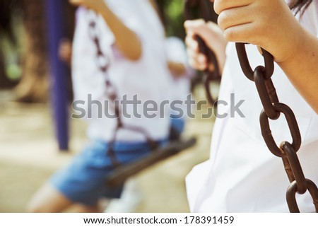 Little child on a swing in the park.  - stock photo