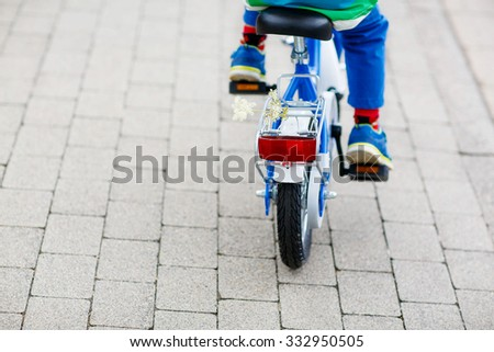 Little child on first bicycle. Active leisure for kids. Child on the way to school. - stock photo
