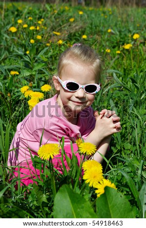 Little Child on green meadow around dandelions