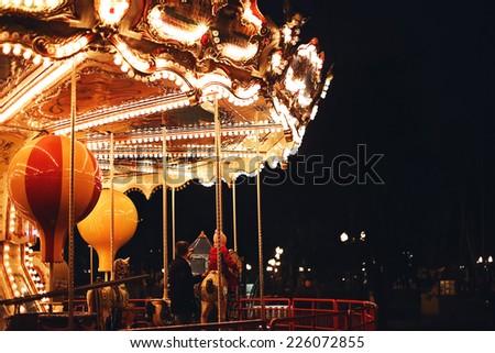 little child on retro carousel - stock photo