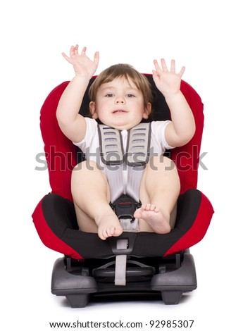 Little child on vehicle car safety seat with belt. Isolated on white. - stock photo