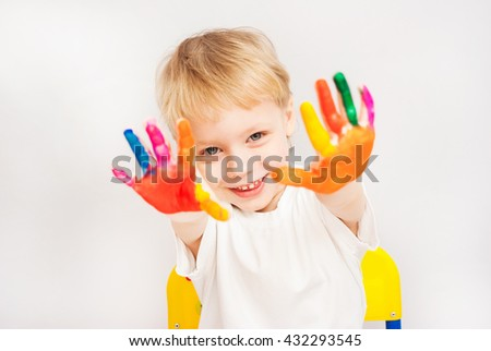Little child painting. Baby boy with hands in paint. Child painted with fingers. Portrait of adorable blond boy isolated on white background. Close up of smiling face and hands of small boy. - stock photo