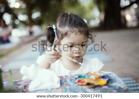 little child painting with colorful paints on white model - stock photo
