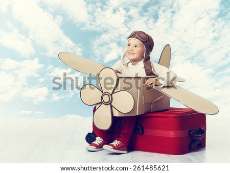 Little Child Playing Airplane Pilot, Kid Traveler Flying in Aviator Helmet on Travel Suitcase, Vacation Trip Concept over Blue Sky Clouds - stock photo