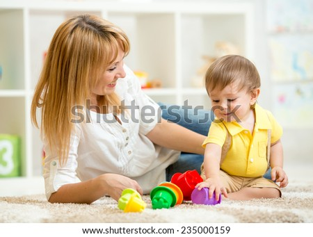 little child playing  and woman with toys - stock photo