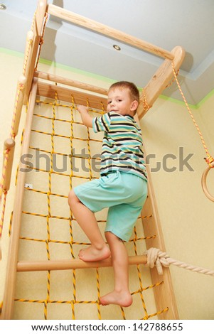 Little child playing sports at sport center. Kid climbing on a rope net. Bottom view.