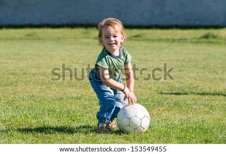 little child playing with ball on football field