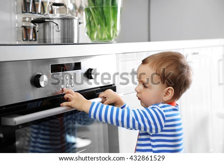 Little child playing with electric stove in the kitchen - stock photo
