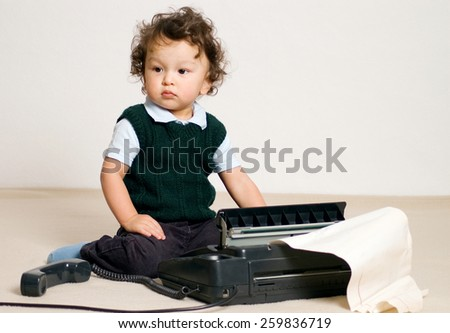 Little child playing with fax.