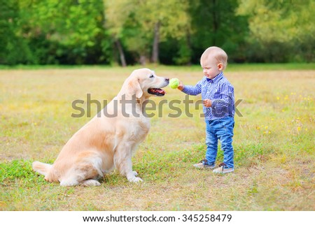 Little child playing with Labrador retriever dog together in park - stock photo