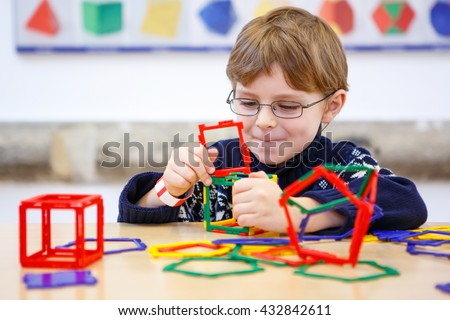 Little child playing with lots of colorful plastic blocks kit in preschool nursery. Happy kid boy having fun with building and creating geometric figures and learning mathematics