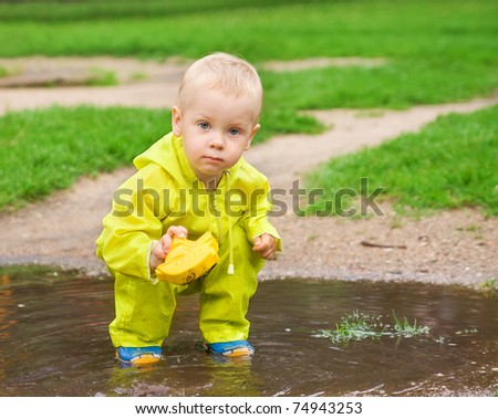 little child playing with ship in the puddle outdoor. Spring season - stock photo
