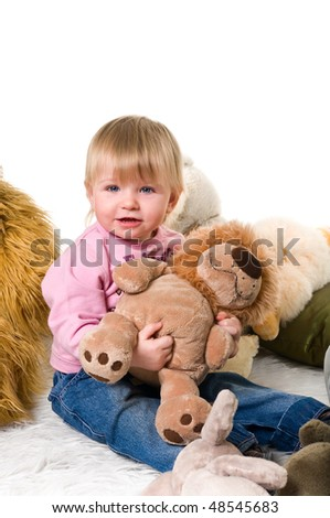 Little child playing with toys on fur carpet. Isolated on white background