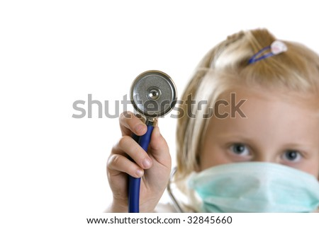 Little child plays doctor with stethoscope and mask - stock photo