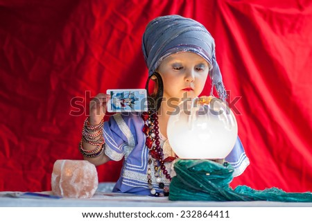 little child plays to be a fortune teller - stock photo