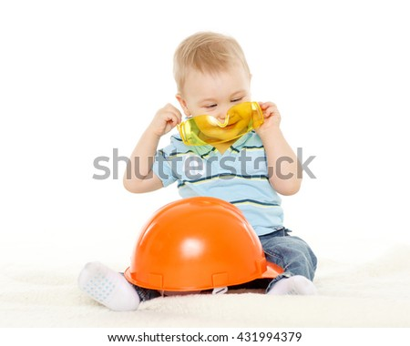 Little child plays with orange construction protective helmet and huge yellow protective eyeglasses on a white background. Profession - future builder. - stock photo